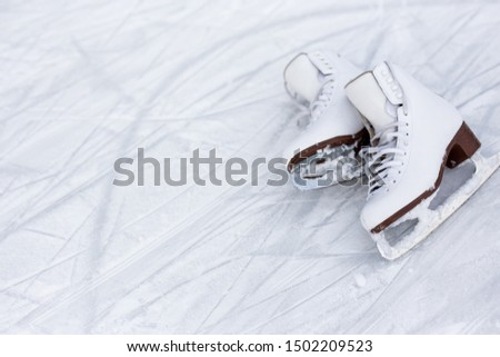 close up of figure skates over ice background with marks from skating or hockey