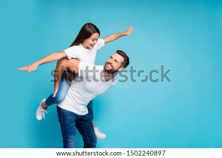 Profile side photo of cheerful people holding hands playing piggyback wearing white t-shirt denim jeans  isolated over blue background #1502240897