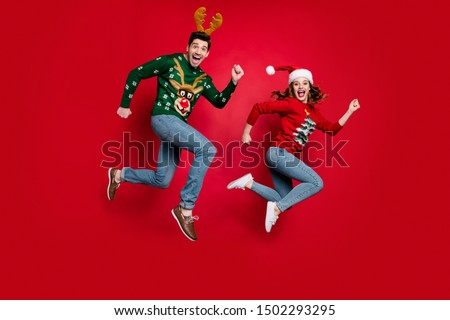 Full length photo of jumping couple excited by x-mas prices hurry buy costumes wear ugly ornament jumpers isolated red color background #1502293295