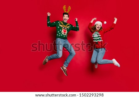 Full length photo of lady and guy jumping excited by x-mas discounts wear ugly ornament jumpers and headwear isolated red color background #1502293298