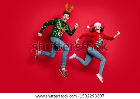 Full length photo of crazy jumping couple excited by x-mas discounts prices wear ugly ornament jumpers isolated red color background #1502293307