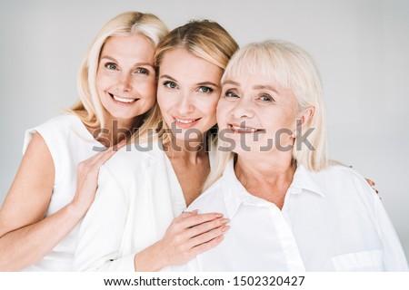 cheerful three generation blonde women isolated on grey Royalty-Free Stock Photo #1502320427