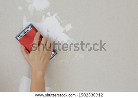 Process of sanding wall with a sanding block after skim coating. Preparation before painting. Renovation house concept.  #1502330912