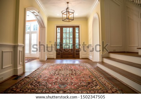 Grand and elegant yellow entrance to a home with stairs. Oriental rug a wood and glass window door. Royalty-Free Stock Photo #1502347505
