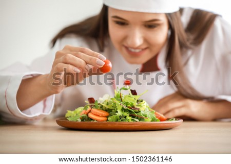 Beautiful female chef with salad in kitchen #1502361146