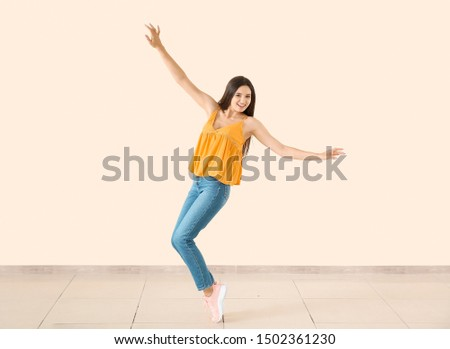 Dancing young woman against light wall #1502361230