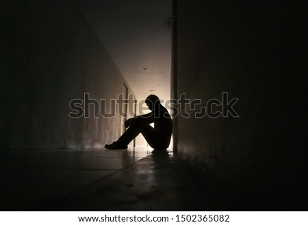 Silhouette of depressed man sitting on walkway of residence building. Sad man, Cry, drama, lonely and unhappy concept. #1502365082