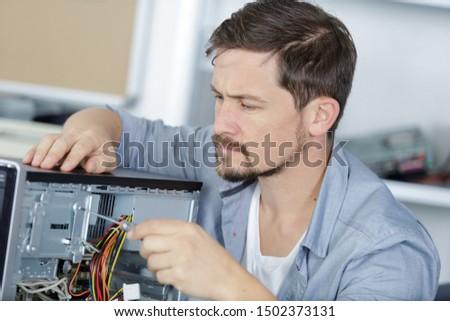 handsome computer technician dismantling laptop #1502373131