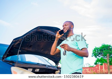 young African man putting a phone call to someone after his car broke down #1502380619