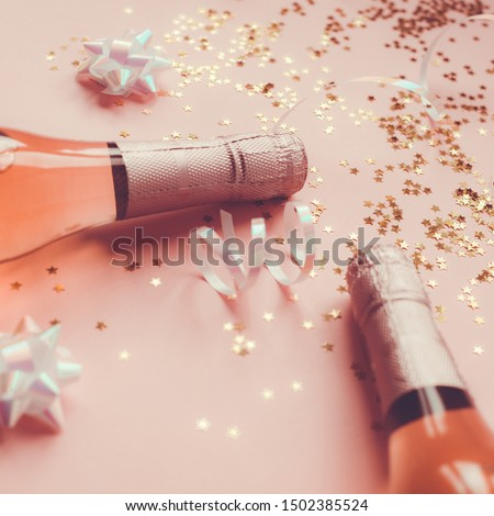 Christmas or New Year composition with bottles of rose champagne and golden shiny sparkle star confetti on pastel pink background, side view. Party Celebration creative concept #1502385524