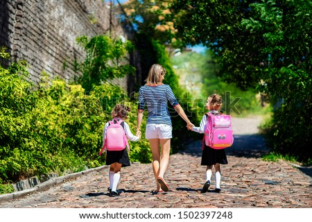 Parent and two pupil of primary school go hand in hand. Woman and girls with backpack behind the back. Beginning of lessons. First day of fall. #1502397248