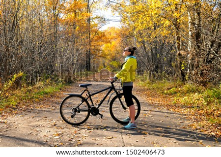 Slim caucasian girl in a yellow jacket poses with a bicycle on the road among the autumn forest #1502406473