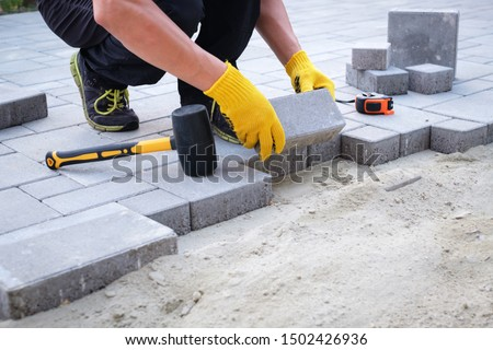 The master in yellow gloves lays paving stones in layers. Garden brick pathway paving by professional paver worker. Laying gray concrete paving slabs in house courtyard on sand foundation base. #1502426936
