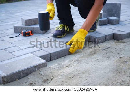 The master in yellow gloves lays paving stones in layers. Garden brick pathway paving by professional paver worker. Laying gray concrete paving slabs in house courtyard on sand foundation base. #1502426984