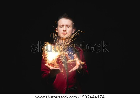 Magician shows trick with fire burn from palms hands. #1502444174