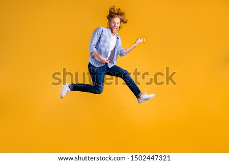 Full length body size photo of crazy funny red haired rock hard rocker man fan wearing jeans denim checkered blue shirt sneakers pretending to play guitar jumping isolated vivid color background #1502447321