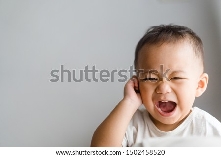 Little toddler boy has earache when insects inside isolated on grey background.2.6 years old baby boy hands touching in ear and screaming. Royalty-Free Stock Photo #1502458520