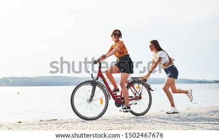 Girl runs near bicycle. Two female friends on the bike have fun at beach near the lake. #1502467676