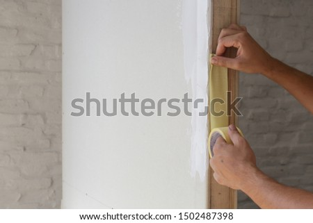 Man putting tape on the wall. The simple step for the quick and easy painting process. Renovation house concept. #1502487398