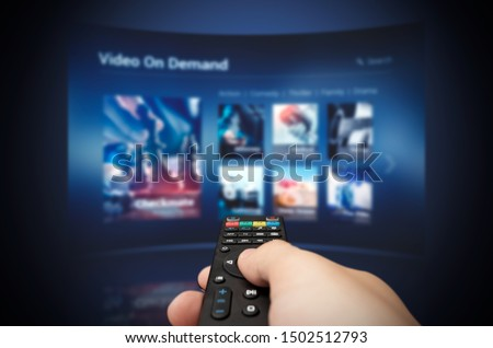 VOD service screen with remote control in hand. Video On Demand television internet stream multimedia concept #1502512793