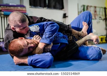 Brazilian Jiu jitsu BJJ jiujitsu training sparring athlete fighter applying deadly rnc rear nacked choke mata leao submission on his opponent technique practice wearing kimono gi #1502514869