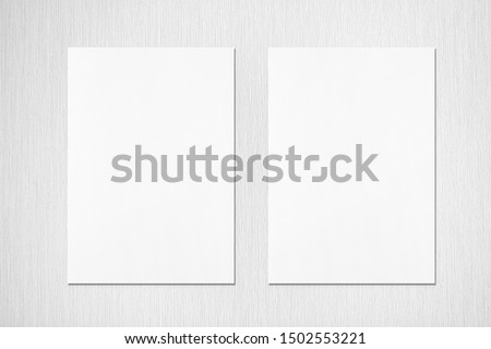 Two empty white vertical rectangle poster mockups with soft shadows on neutral light grey textured background. Flat lay, top view