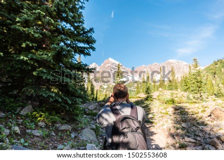 Maroon Bells peak view in Aspen, Colorado with tourist man backpack hiker taking picture with phone or camera in July 2019 summer on trail path road wide angle view