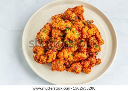 Buffalo Cauliflower Wings on a Baking Sheet.  Popular Baked Cauliflower Appetizer Photo.. Barbecue Cauliflower Wings - Vegan Food #1502635280