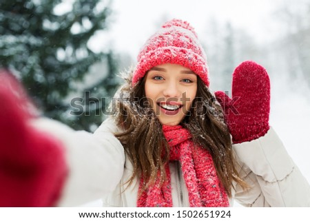 christmas, season and people concept - happy smiling woman taking selfie and waving hand outdoors in winter park