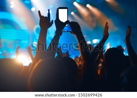 Hands with a smartphone records live music festival, Taking photo of concert stage. #1502699426