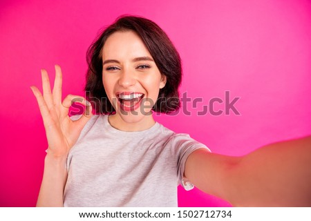 Self portrait of charming cheerful attractive nice cute girlfriend showing you ok sign taking selfie wearing grey t-shirt assessing joke quality while isolated with fuchsia bright color background