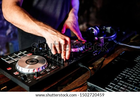 DJ plays live set and mixing music on turntable console at stage in the night club. Disc Jokey Hands on a sound mixer station at club party. DJ mixer controller panel for playing music and partying. #1502720459