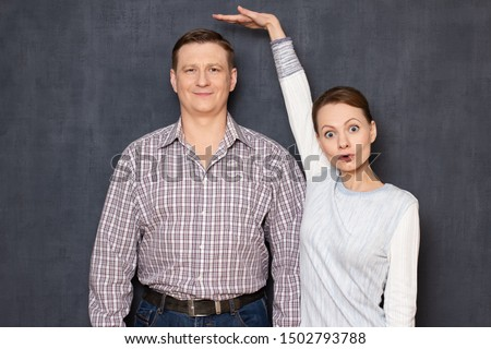 Studio half-length shot of amazed short woman pulling up and showing with hand at height of happy tall man standing beside her and smiling cheerfully, over gray background. Variety of person's heights #1502793788