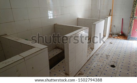 CLOSE UP: Empty public toilets in remote Tibetan town with waist high dividers. Dreary view of smelly squat latrines in China separated by only short walls. Unhygienic restrooms with no privacy. #1502794388