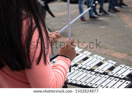 """Close up for girl playing """"lira"""" a musical instrument for a martial band in bogotá, Colombia downtown street."""