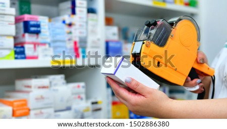 Hand of the pharmacist using yellow labeling gun for sticking price label of medicine in pharmacy drugstore.banner size #1502886380