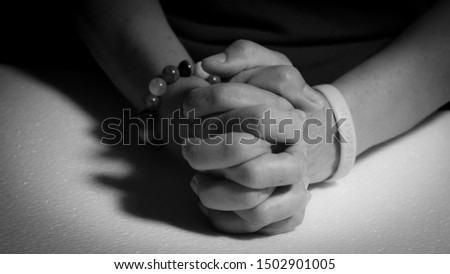 Women holding hands and praying black and white pictures