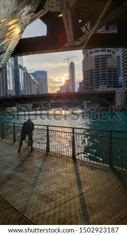 young traveling tourist photographer is taking pictures of the architecture under a Chicago bridge during sunset golden hour. the Chicago river illuminated from the sun as he is silhouetted