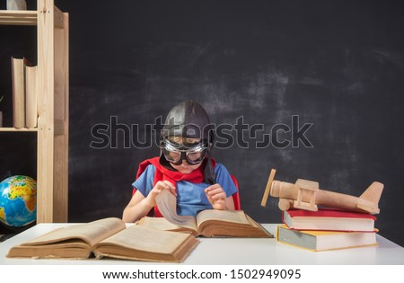 Child sitting the desk and reading a book while playing pilot. Child pilot in helmet and glasses with wooden toy airplane. Innovation and bright idea. Picture of bulb on blackboard