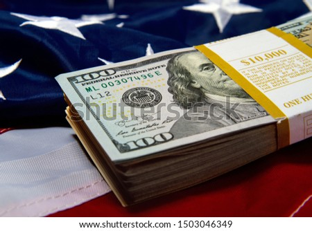 a pack with ten thousand dollars in hundred dollar bills lies against the backdrop of a starry striped American flag #1503046349