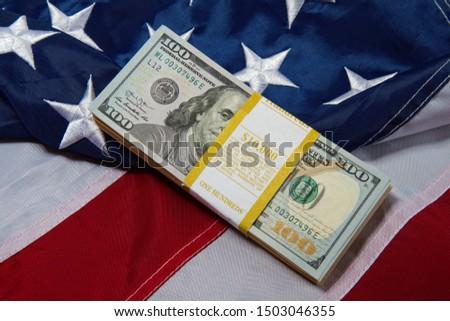 a pack with ten thousand dollars in hundred dollar bills lies against the backdrop of a starry striped American flag #1503046355