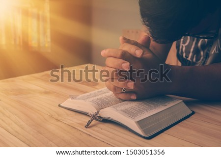 Christian hand while praying and worship for christian religion with blurred of her body background, Casual man praying with her hands together over a closed Bible. christian background. freedom. #1503051356