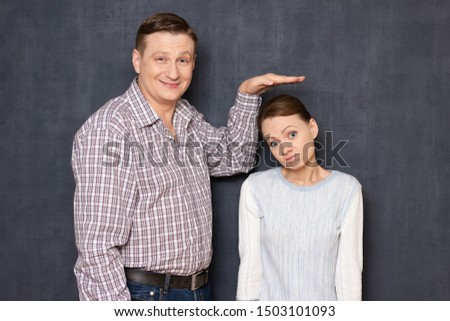 Studio half-length shot of happy tall man showing with hand at height of upset short girl standing beside him and looking with perplexity at camera, over gray background. Variety of person's heights #1503101093