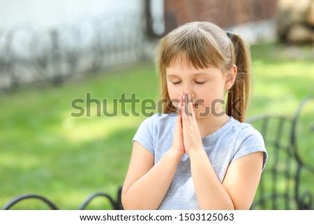 Cute little girl praying outdoors #1503125063