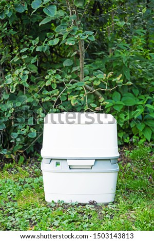 Chemical portable toilet. Single portable toilet standing on a green nature courtyard background   #1503143813