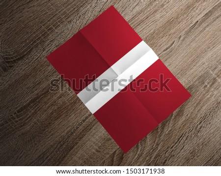 Flag of Latvia on paper. Latvia Flag on wooden table. #1503171938