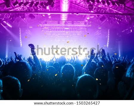 Musical event with people silhouettes clapping a live stage Royalty-Free Stock Photo #1503265427