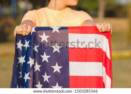 Woman with a flag of United States of America in the hands, outdoors, soft focus background #1503285566