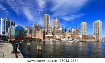 Boston skyline with skyscrapers reflections into the ocean and waterfront promenade on the foreground, Massachusetts, USA
