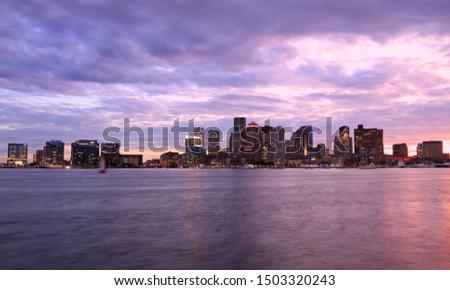 Boston skyline at sunset, with purple sky and ocean, Massachusetts, USA